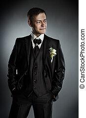 Handsome man in black suit. Grey background.