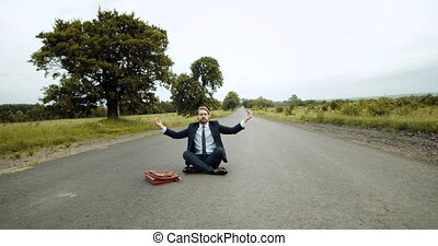 Handsome man in black suit meditating on countryside road