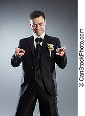 Handsome man in black suit pointing fingers in front of himself. Indicate forward. Grey background.