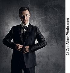 Handsome man in black suit. Wedding groom fashion. Gray background.