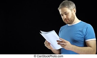 Handsome man in blue tshirt looking through papers. Cotract, bills, letter concepts. Black background.