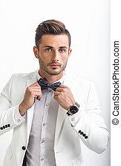 Handsome man in elegant suit adjusting his bow tie