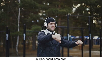 Handsome man in headphones doing stretching exercise while listening music in winter park