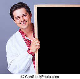 Handsome man in national embroidery with blackboard.