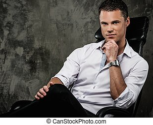 Handsome man in shirt against grunge wall sitting in office chair