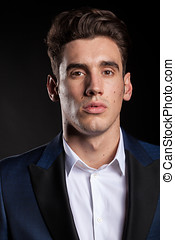 Handsome man in suit on black background
