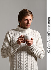 Handsome man in sweater drinking tea