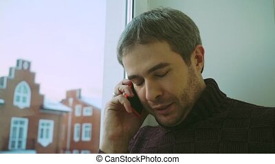 Handsome man in sweater speaking on his phone by the window to townhouses
