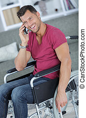 handsome man in wheelchair talking on his phone and smiles