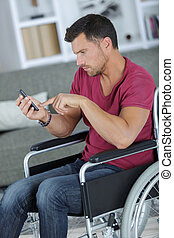 handsome man in wheelchair texting on his phone