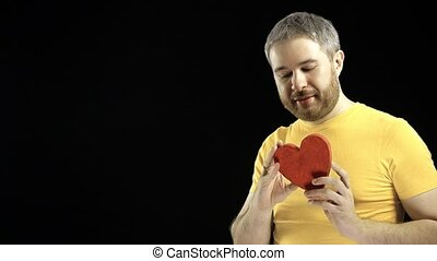 Handsome man in yellow tshirt holds red heart shape. Love, romance, dating, relationship concepts. Black background.