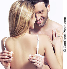 handsome man is unfastening the bra for the woman