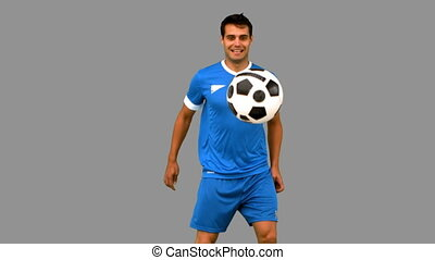 Handsome man juggling a football on grey screen in slow ...