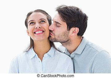 Handsome man kissing girlfriend on cheek