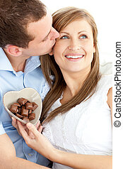 Handsome man kissing his girlfriend holding chocolote...