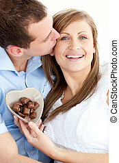 Handsome man kissing his girlfriend holding chocolote