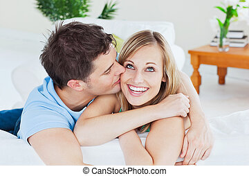 handsome man kissing his joyful girlfriend both lying on the...