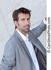 Handsome man leaning on grey wall