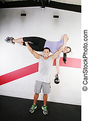 Handsome man lifting a beautiful woman at the gym