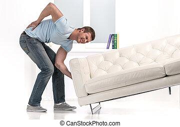Handsome man lifting sofa and feeling pain. man droped sofa...