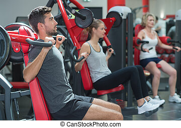handsome man lifting weights in gym and staying fit