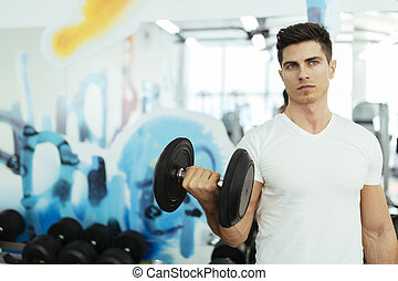 Handsome man lifting weights in gym