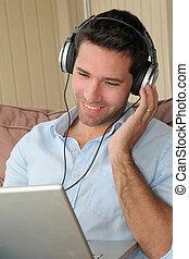 Handsome man listening to music on internet
