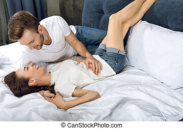 man looking at laughing woman while lying in bed
