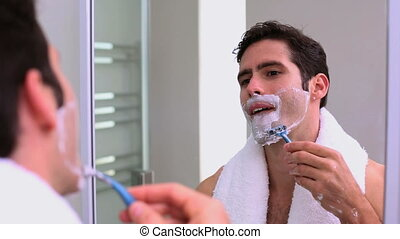 Handsome man looking at mirror and shaving
