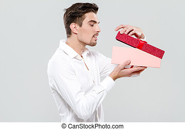 Handsome man looking in pink box