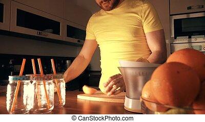 Handsome man making fresh orange juice with a juicer at home.