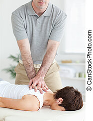 Handsome Man massaging a cute woman's neck in a room