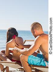 Handsome man massaging his girlfriend with sun cream