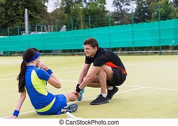 Handsome man massaging woman's injured leg after  tennis match