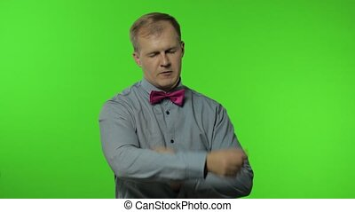 Handsome playful man moving in dance, smiling carefree, trends, gesture of success, internet meme, celebrate. Portrait of guy posing isolated on chroma key background in studio. People emotions