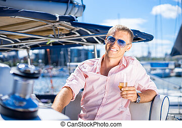 Handsome man on a boat - Handsome man relaxing on a sailing...