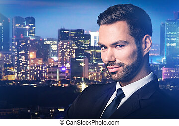 Handsome man on city at night background.