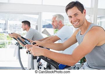 Handsome man on exercise bike