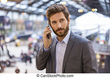 Handsome man on the mobile phone in hall station