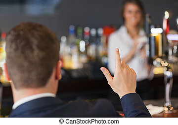 Handsome man ordering a drink from pretty waitress in a ...