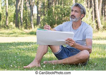 handsome man painting a spring landscape