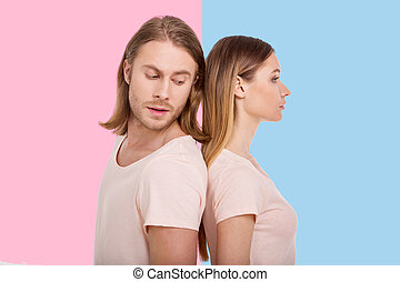 Handsome man peeking at woman while standing back-to-back