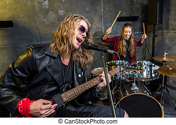 Handsome man playing electric guitar and woman sitting at drums set in musical studio
