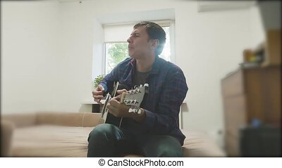 Handsome man playing guitar. Man Playing Acoustic Guitar Close Up slow motion video. in the room sits on the couch. man and guitar concept lifestyle