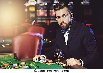 Handsome man playing roulette in the casino