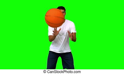 Handsome man playing with a basketball