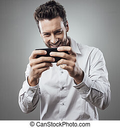 Handsome man playing with his smartphone