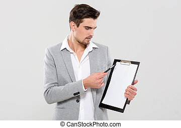 Handsome man pointing on clipboard