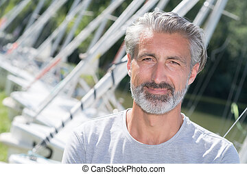 handsome man posing in front of sailing boats and lake