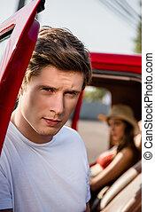 handsome man posing near car